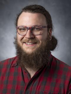 Bearded man with ponytail wearing glasses
