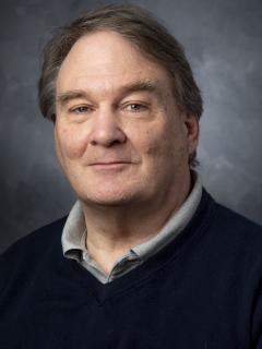 Man with brown hair wearing grey shirt and navy pullover sweater