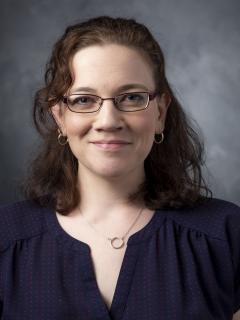 Woman with shoulder length wavy reddish brown hair. She's wearing glasses and a dark blue shirt.