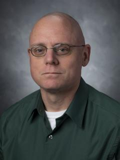Man wearing glasses and a green button down shirt.