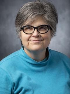 Woman with short hair wearing glasses and an aqua turtleneck.