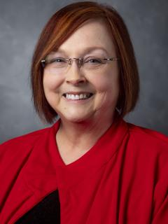 Woman with chin length bobbed red hair. She's wearing glasses and a red jacket over a black shirt.